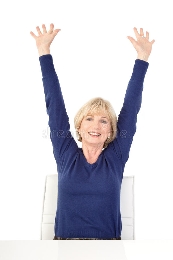 Happy senior woman sitting with raised arms, isolated on white b stock images