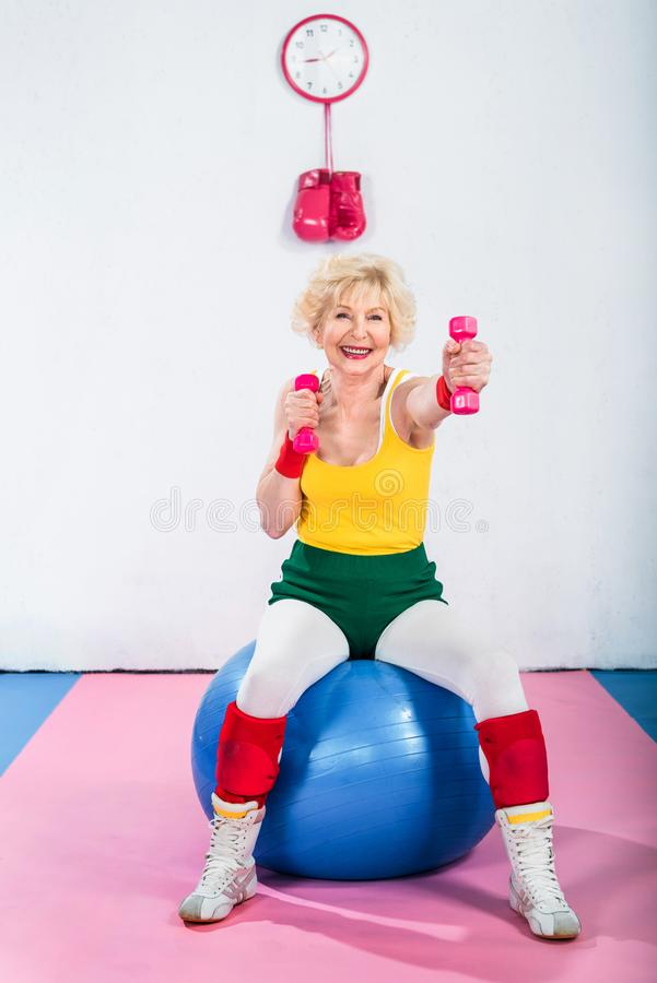 happy senior woman in sportswear sitting on fitness ball and exercising royalty free stock photo