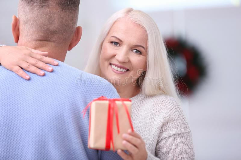 Happy senior woman with Christmas gift hugging her husband at home stock photo