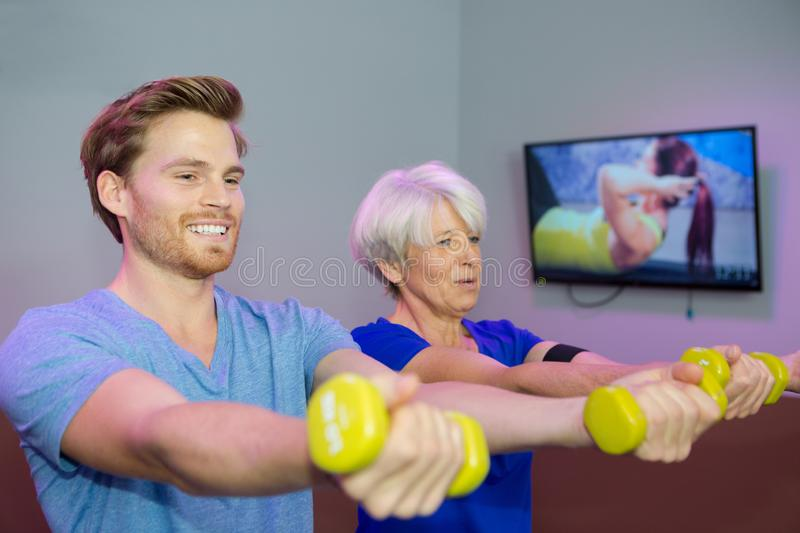 Happy senior woman exercising with dumbbells and trainer royalty free stock photos