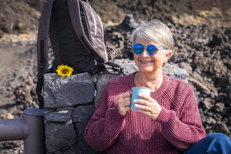 Happy senior years old mature retired beautiful lady with white hair enjoying the outdoor leisure activity lifestyle and drink royalty free stock photography