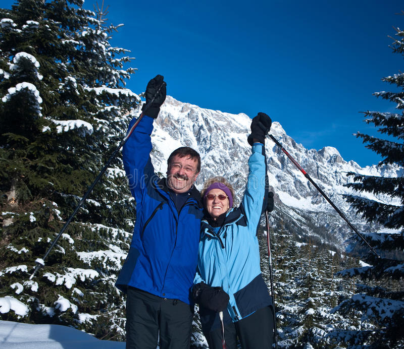Happy seniors. A senior couple in a winter setting in the alpine mountains. Active and happy seniors stock photography