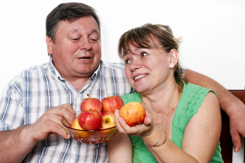 Happy seniors couple with apple. Isolated over white background stock images