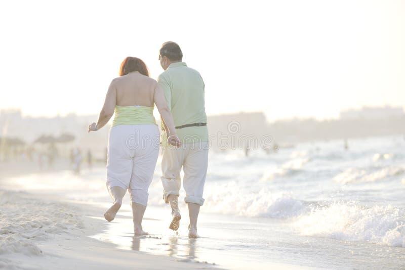 Happy seniors couple on beach stock images