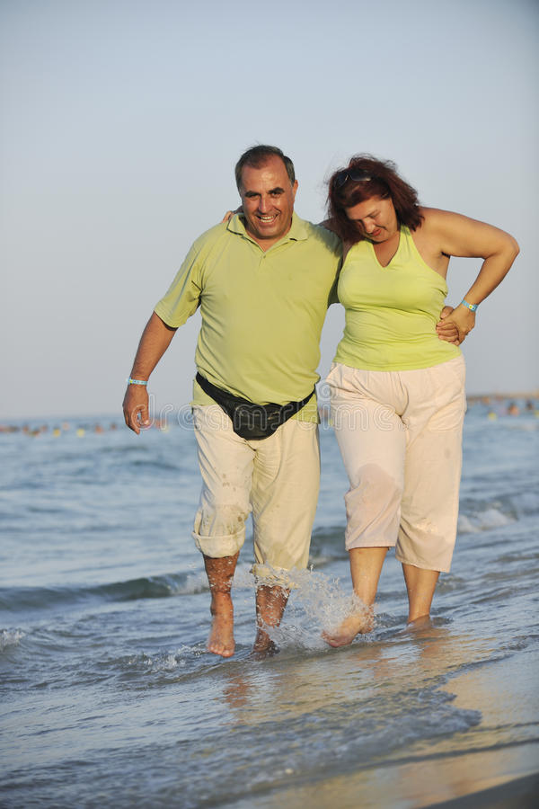 Happy seniors couple on beach. Happy senior mature elderly people couple have romantic time on beach at sunset stock images