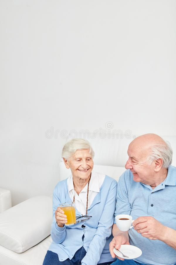Happy seniors couple is drinking a cup of coffee stock photos