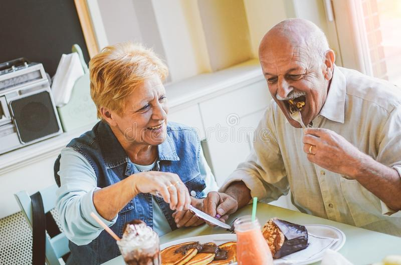 Happy seniors couple eating pancakes in a bar restaurant - Mature people having fun dining together at home. Concept of elderly lifestyle moments - Vintage royalty free stock photo