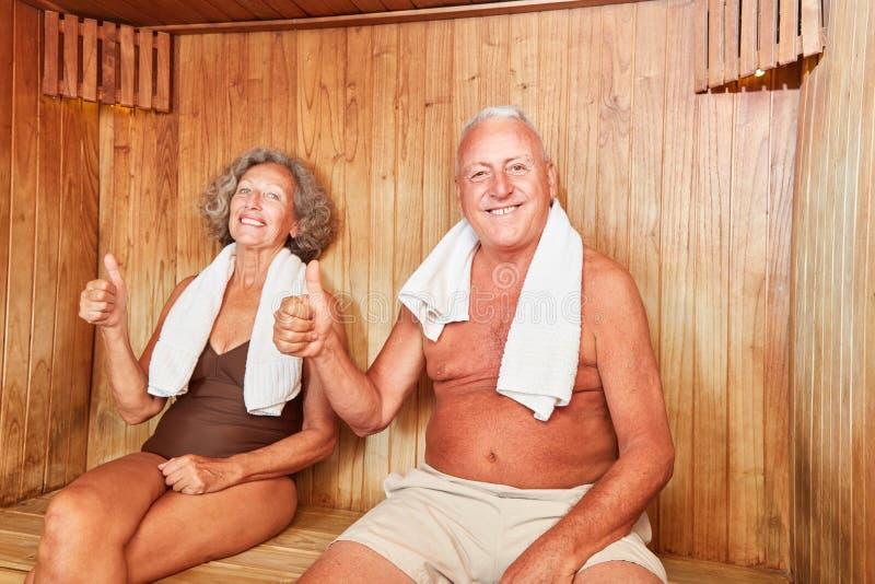 Happy seniors couple is enjoying the sauna. Happy seniors couple enjoys the sauna for wellness and health royalty free stock image