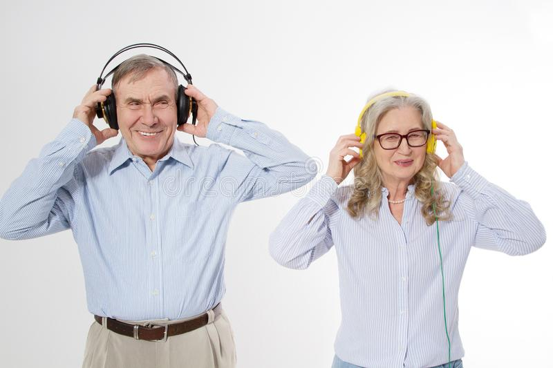 Happy seniors couple lesten to music in headphones isolated on white background. Elderly family fun disco and pisitive healthy old royalty free stock photo