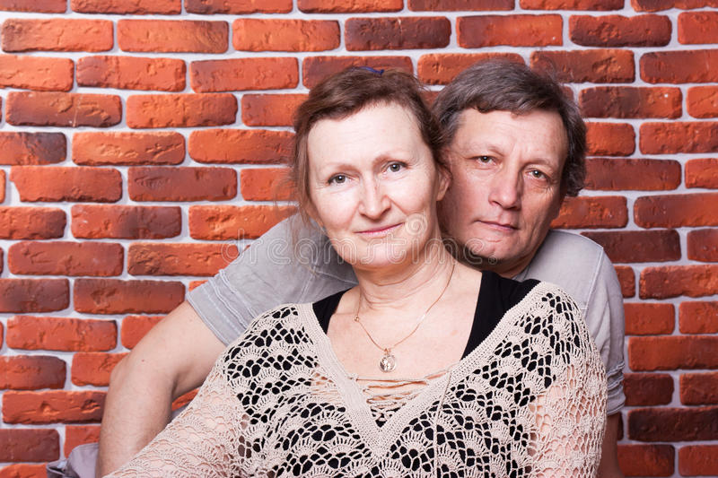 Happy seniors couple in love. Against brick wall stock photo