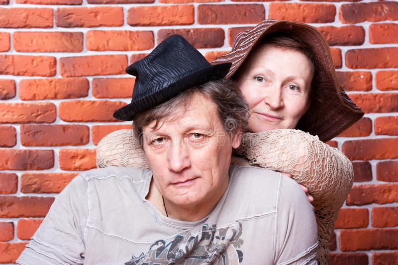 Happy seniors couple in love in hats. Against brick wall royalty free stock photos