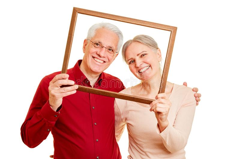Happy seniors couple in picture frame. Happy seniors couple is looking through a blank picture frame royalty free stock image