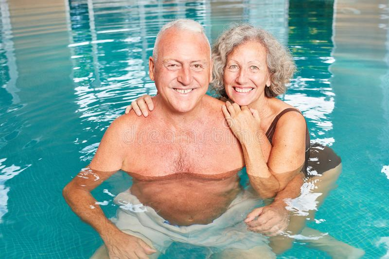 Happy seniors couple in the pool. Happy seniors couple together in the pool on spa vacation at the hotel stock photography