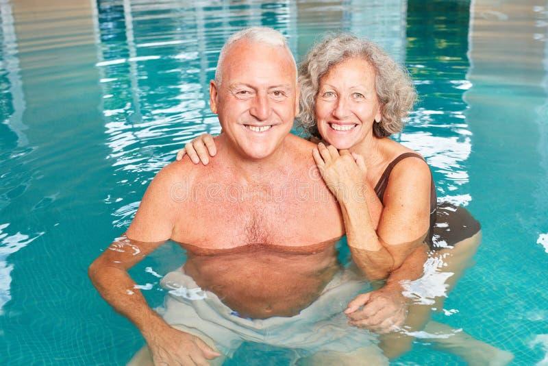 Happy seniors couple in the pool stock photography