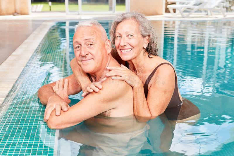 Senior couple relaxes in the pool. Happy seniors couple relaxing by the poolside poolside at the wellness hotel royalty free stock photography