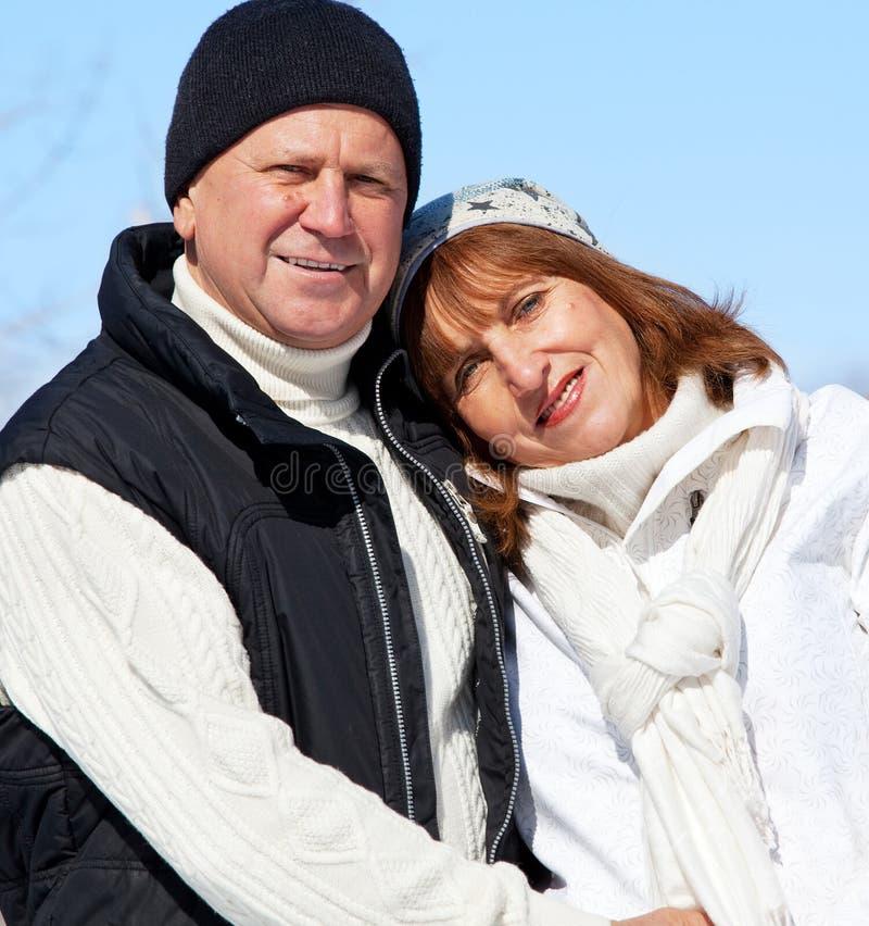 Happy seniors couple in winter park. Elderly mature people stock image