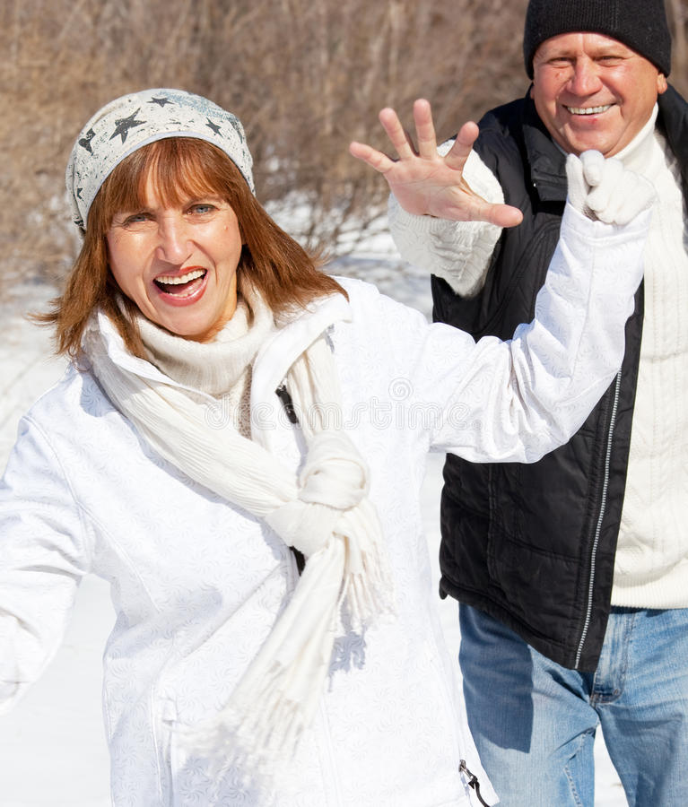 Happy seniors couple in winter park. Elderly mature people royalty free stock photography