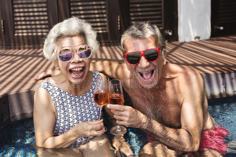Happy seniors drinking prosecco in the pool stock images