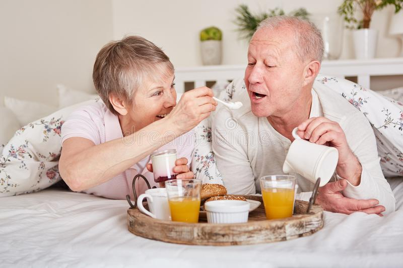 Happy seniors having breakfast in bed stock photo