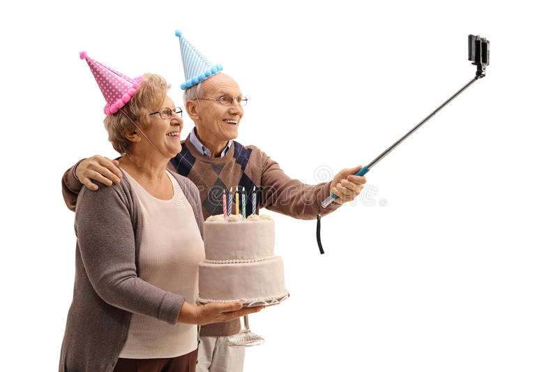 Happy seniors with party hats and a birthday cake taking a selfie. With a stick isolated on white background stock image