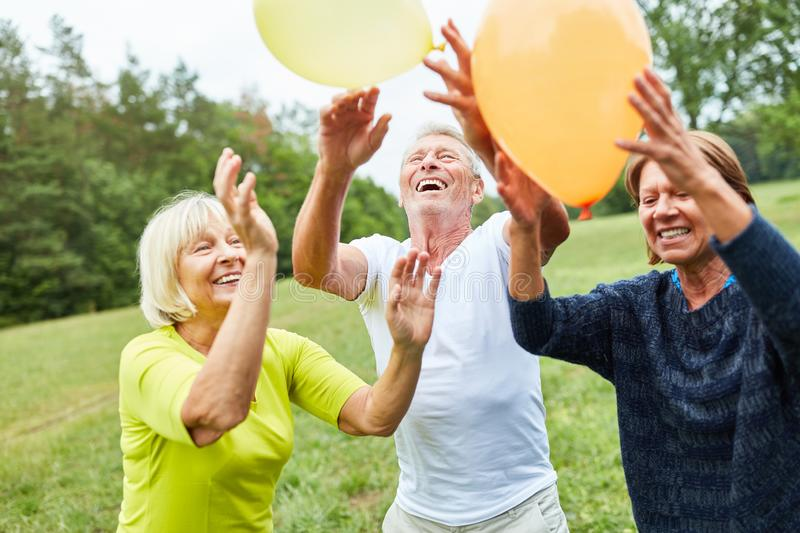 Happy seniors play with balloons. Happy seniors playing with balloons at a summer party in the park stock images