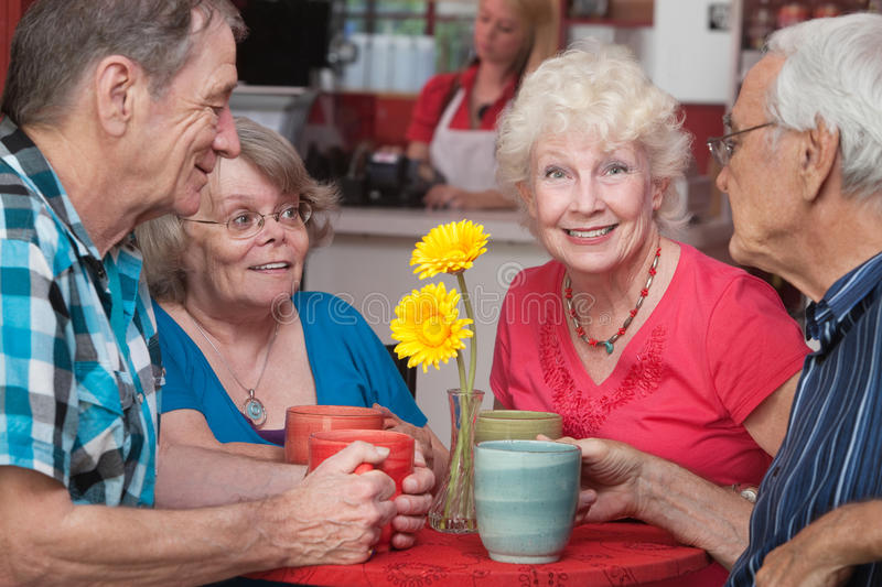 Happy Seniors at Restaurant. Group of four happy senior citizens at restaurant stock photography