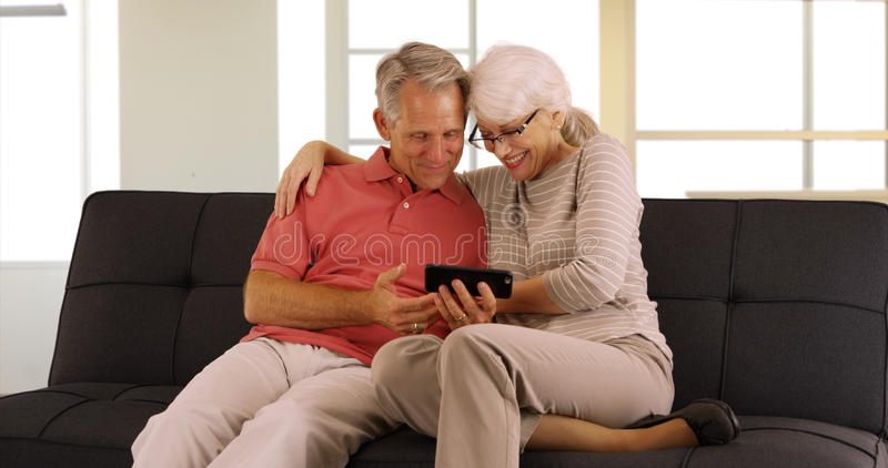 Happy seniors sitting on couch watching videos on smartphone stock images