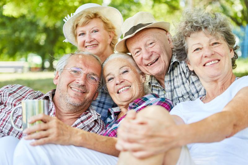 Happy seniors on a summer outing. Happy seniors group as friends on a tour in summer in nature royalty free stock photo