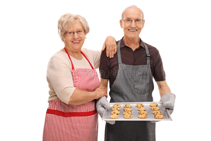 Happy seniors with a tray of freshly baked cookies stock photography