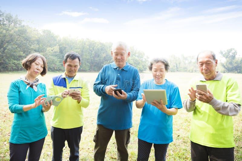 Happy seniors using smart phone stock photography