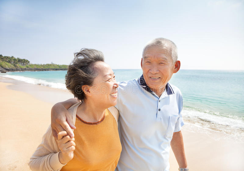 Happy seniors walking on the beach stock photos
