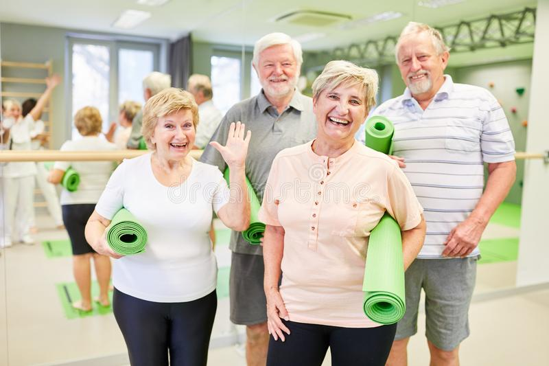 Happy seniors with yoga mats in the gym. Are looking forward to the back exercises stock photo