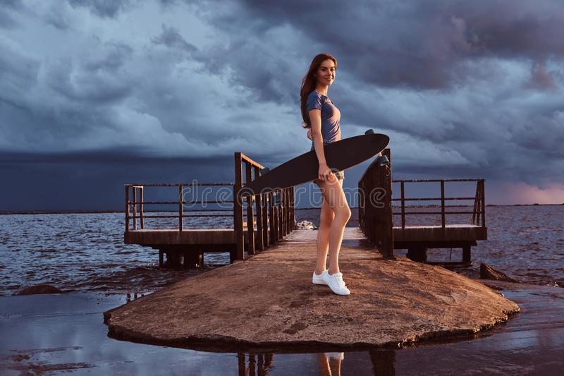 Portrait of a sensual girl holds a skateboard while standing on the beach is enjoying amazing dark cloudy weather during stock photography