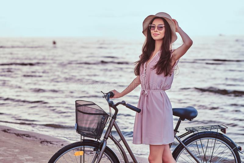 Happy sensual girl in sunglasses and hat wearing dress walks with her bicycle on the beach against an amazing seaside stock photo