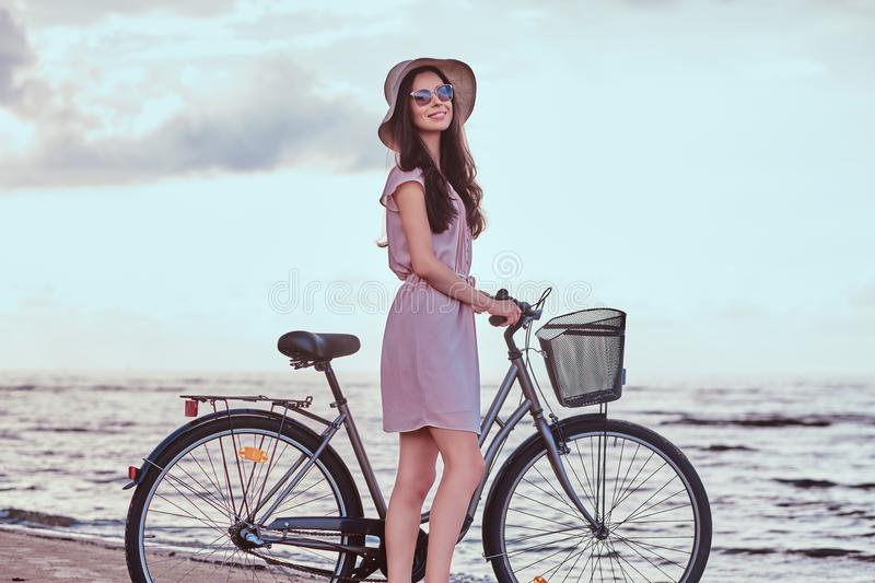 Happy sensual girl in sunglasses and hat wearing dress walks with her bicycle on the beach against an amazing seaside stock photography