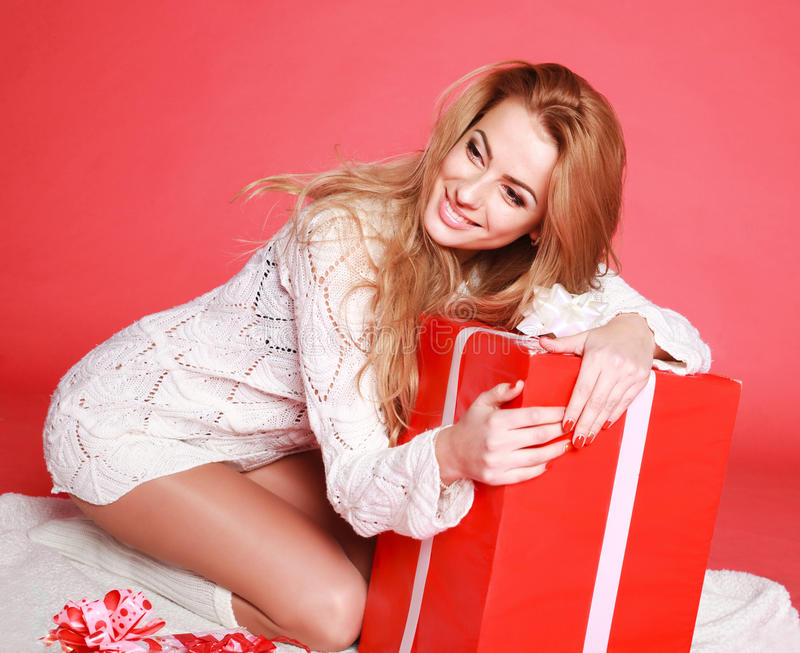 Happy sensual woman with christmas gifts. Studio on pink background royalty free stock image