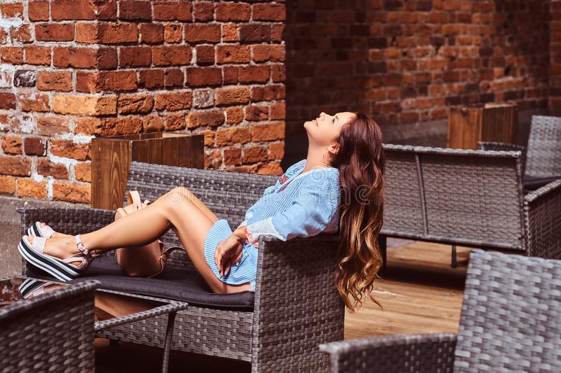 Happy sensual woman with long brown hair dressed in trendy clothes relaxing while sitting at the cafe. stock photo