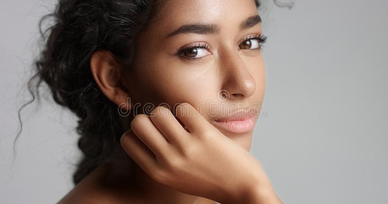 Happy serene young woman with beautiful olive skin and curly hair ideal skin and brown eyes in studio stock images