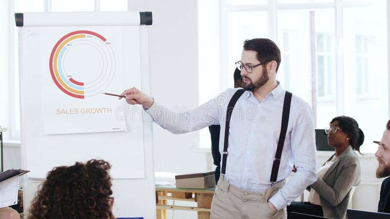 Happy serious successful young coach businessman explaining marketing chart to multiethnic group at office meeting. royalty free stock photos