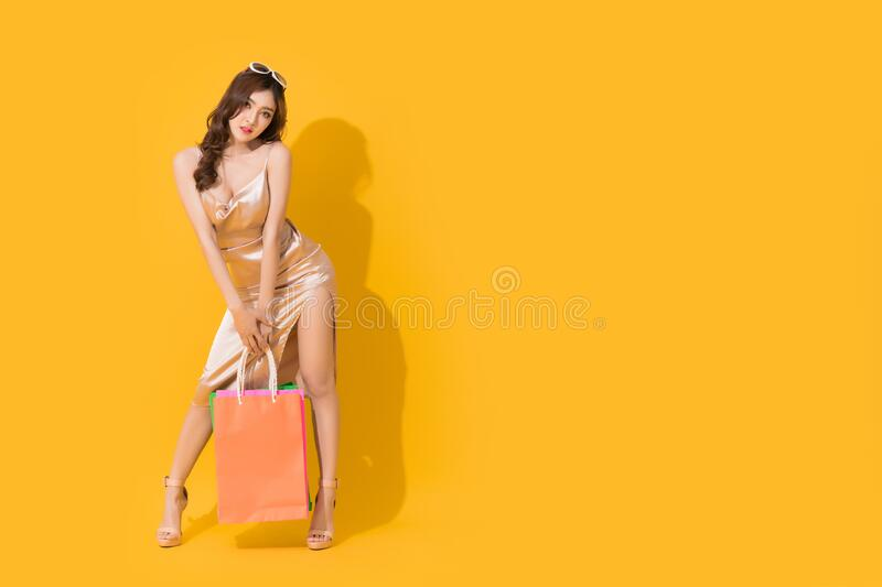 Happy Sexy Asian shopaholic woman carrying shopping bags in colorful orange and yellow background royalty free stock image