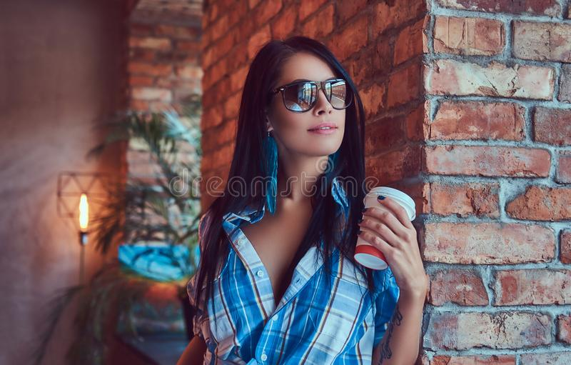 A happy brunette in flannel shirt and sunglasses holds a cup of coffee posing against a brick wall. royalty free stock images