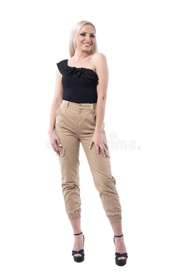 Happy sexy young blond hair woman in creme pants and off shoulder top posing. royalty free stock photography