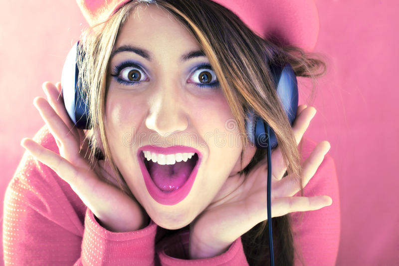 Happy shocked woman in pink listening to good sound royalty free stock photography