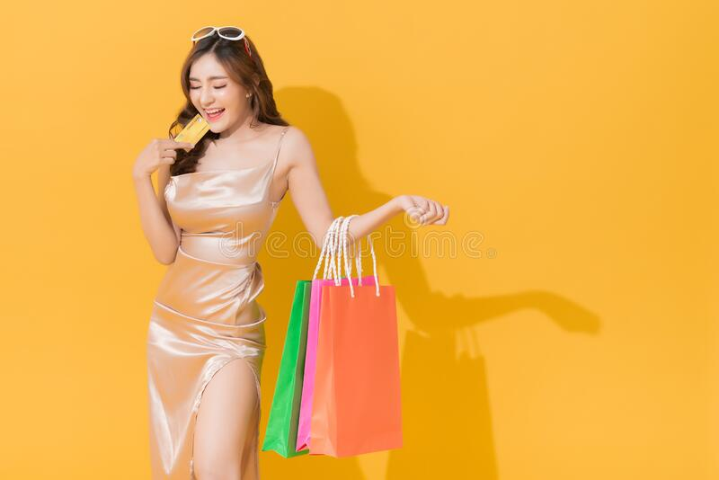 Happy shopaholic woman carrying shopping bags in colorful orange and yellow background royalty free stock images