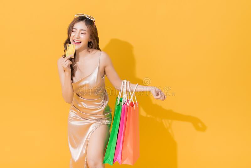 Happy shopaholic woman carrying shopping bags in colorful orange and yellow background stock photo