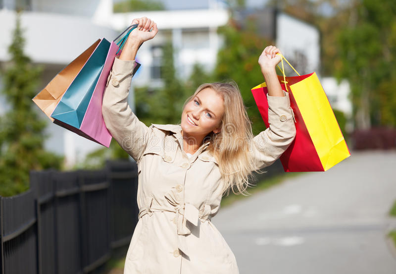 Happy shoper. Happy woman with full bags of new stuff walking on the street royalty free stock photo