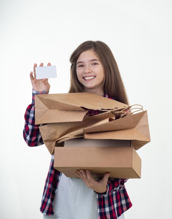 Happy shopper holding discount white card and shopping bags and carton boxes in her hands. Young girl with credit card. stock photos