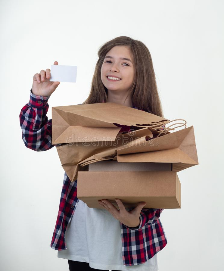 Happy shopper holding discount white card and shopping bags and carton boxes in her hands. Young girl with credit card. royalty free stock photo