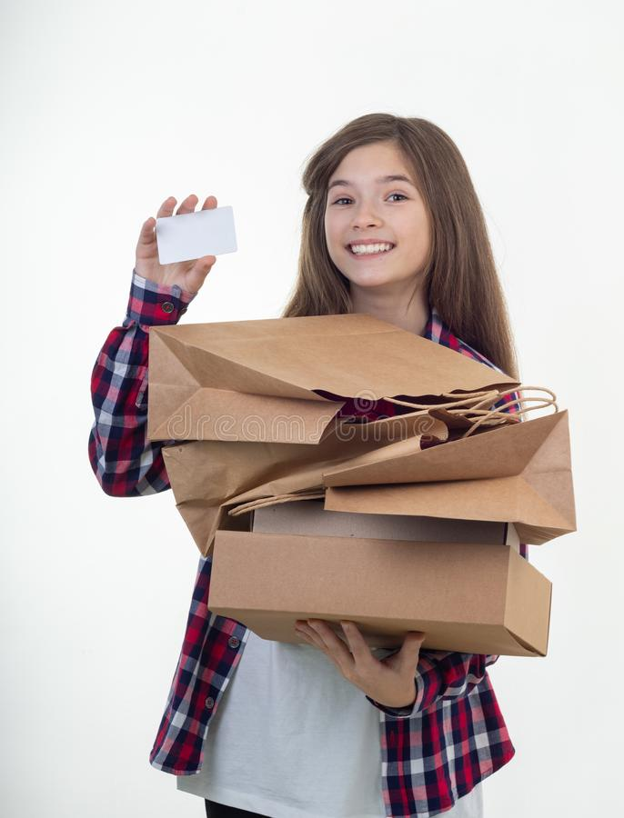 Happy shopper holding discount white card and shopping bags and carton boxes in her hands. Young girl with credit card. stock image