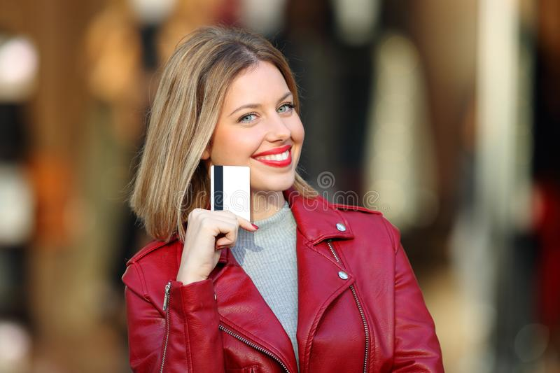 Happy shopper showing blank credit card in a mall. Happy shopper showing blank credit card looking at camera in a mall stock photography